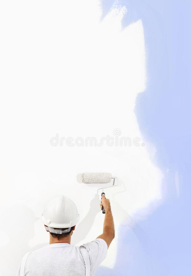 Rear view of painter man with paint roller painting on blank wall, isolated on white, copy space stock photos