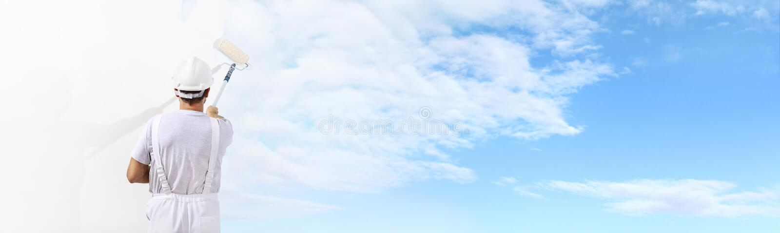 Rear view of painter man painting the blue sky on blank wall stock image