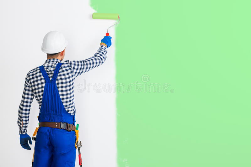 Rear view of painter man painting the wall in green royalty free stock images