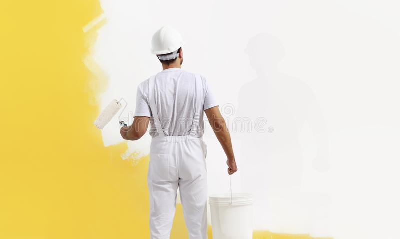 Rear view of painter man painting the wall, with paint roller and bucket, isolated on big empty copy space royalty free stock photography