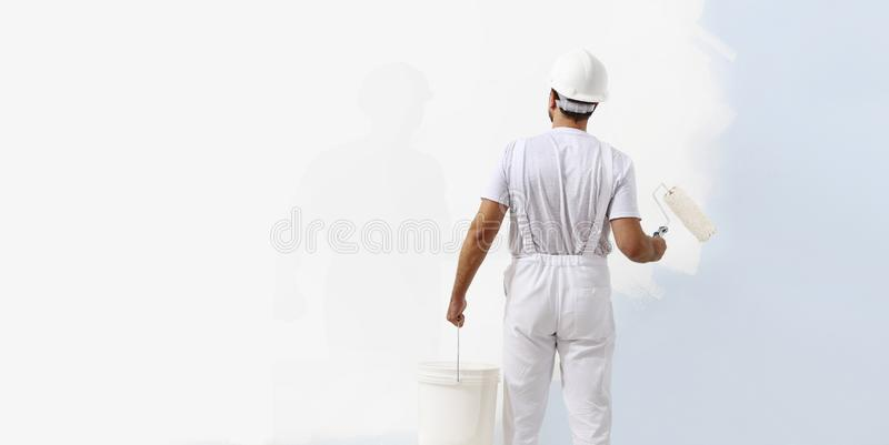 Rear view of painter man painting the wall, with paint roller and bucket, isolated on big empty white copy space stock photography