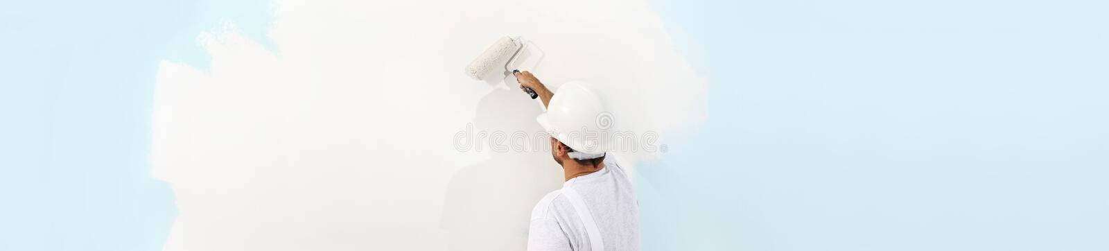 Rear view of painter man painting the wall, with paint roller, i royalty free stock photography