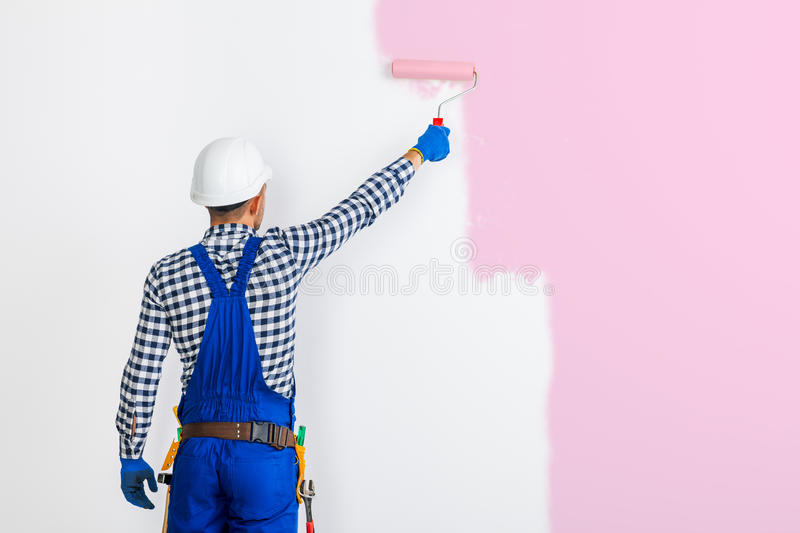 Rear view of painter man painting the wall in pink stock photo