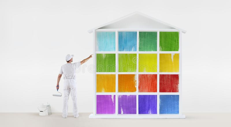 Rear view of painter man pointing with finger the colors house m royalty free stock image