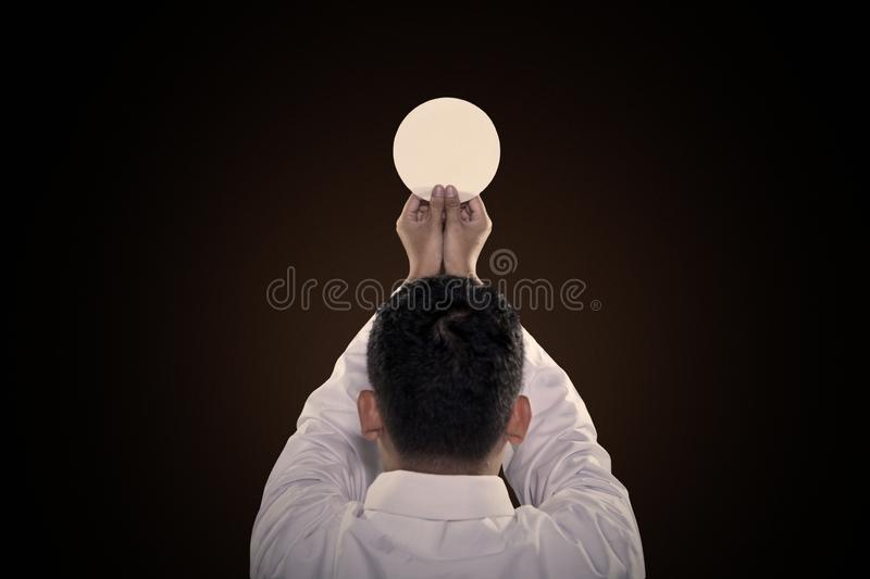 Pastor prays to God consecration a bread. Rear view of pastor praying to God consecration a communion bread in the dark background stock photos