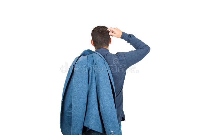 Rear view of pensive young businessman, hand to head thoughtful gesture, keeps his jacket on shoulder, isolated on white royalty free stock photos