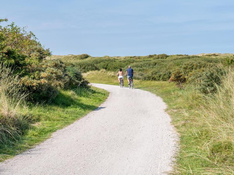 Rear view of people riding bikes on bicycle path in dunes of nature reserve Het Oerd on West Frisian island Ameland, Netherlands royalty free stock photos