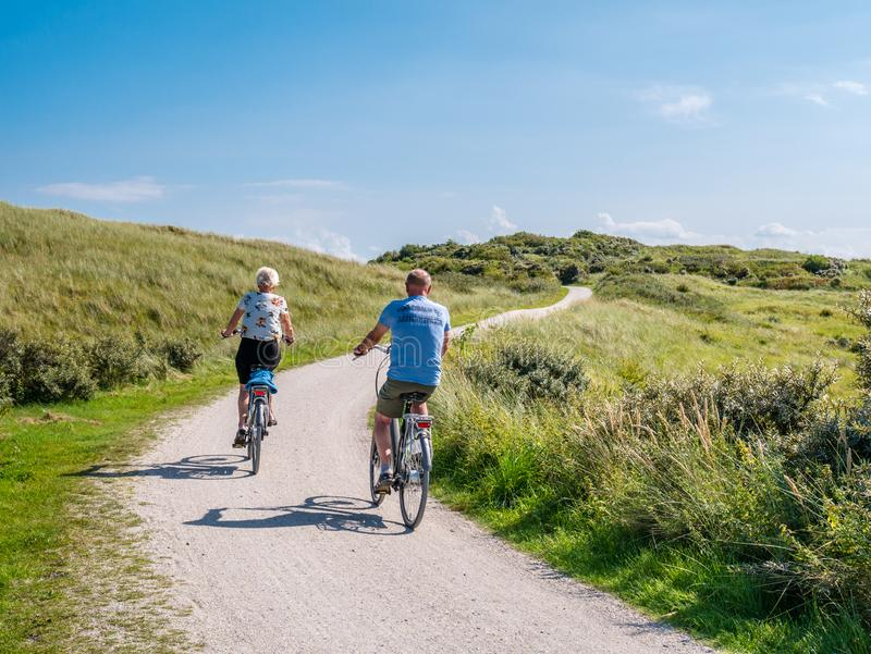 Rear view of people riding bikes on bicycle path in dunes of nature reserve Het Oerd on West Frisian island Ameland, Netherlands stock photography