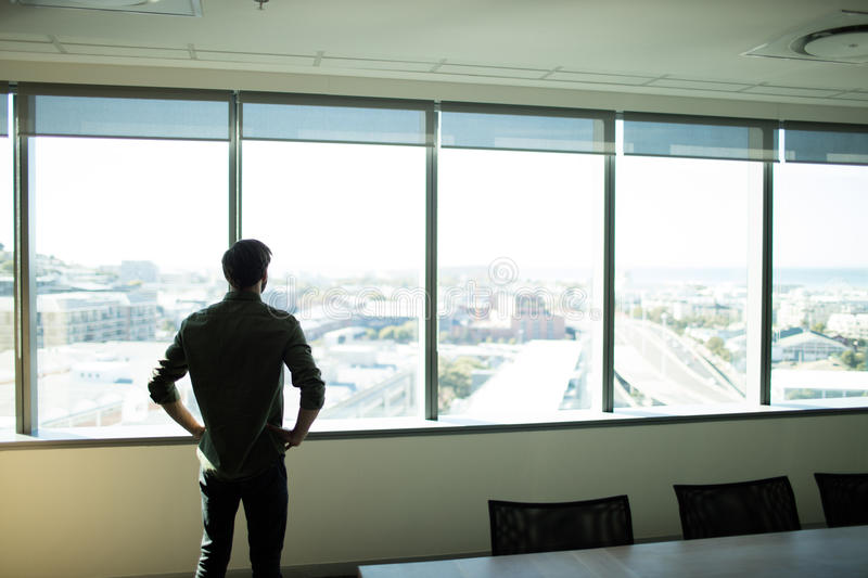 Rear view pf businessman looking through window at workplace stock photos