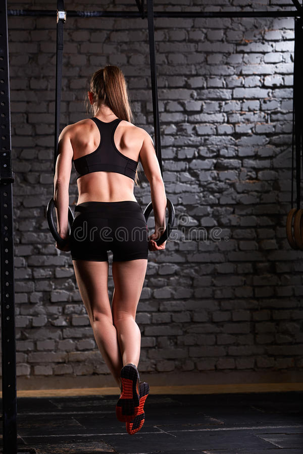 Rear view photo of the beautiful female sporty woman using rings equipment in cross fit gym against brick wall. royalty free stock image
