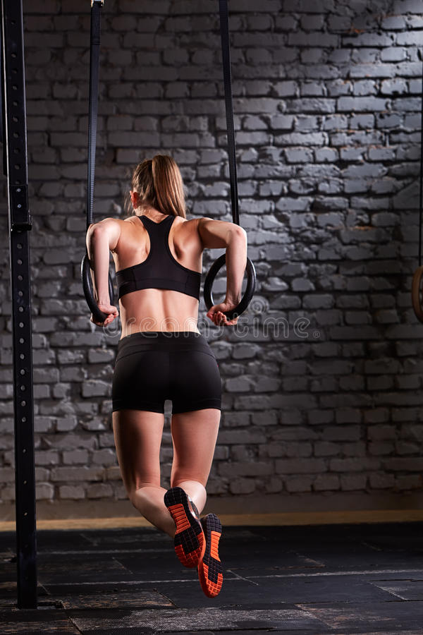 Rear view photo of beautiful young sporty woman in the black sportwear doing pull-ups exercise using gymnastic rings. stock photo