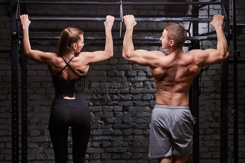 Rear view photo of muscular man and woman doing exercises on horizontal bar against brick wall at the cross fit gym. Rear view photo of muscular men and women royalty free stock image
