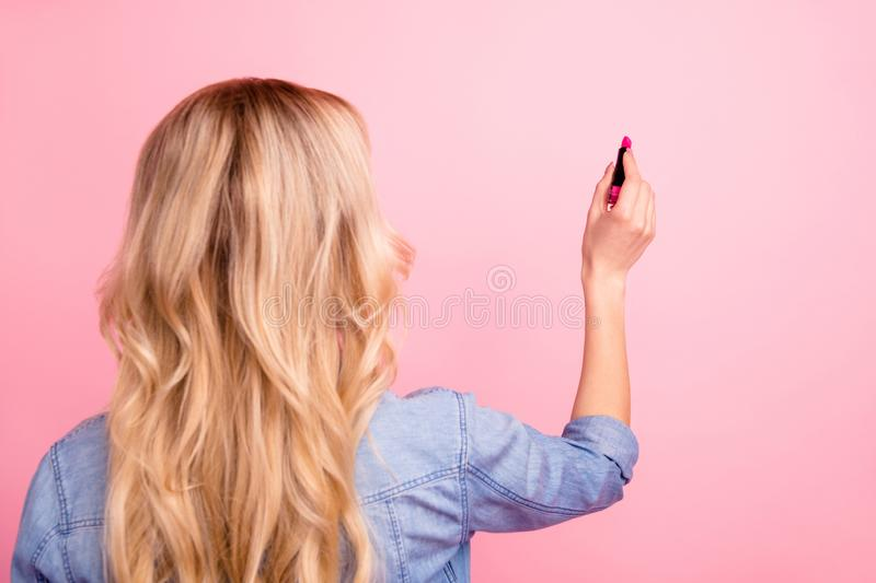 Rear view photo of pretty lady testing new pomade quality on wall wear denim outfit isolated pink background stock photo