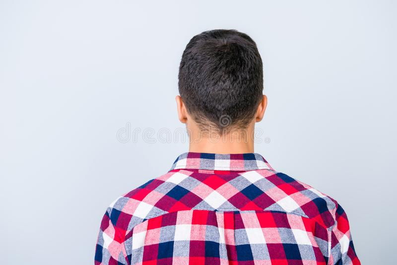 Rear view photo of young brunet hipster with modern haircut, in royalty free stock photography
