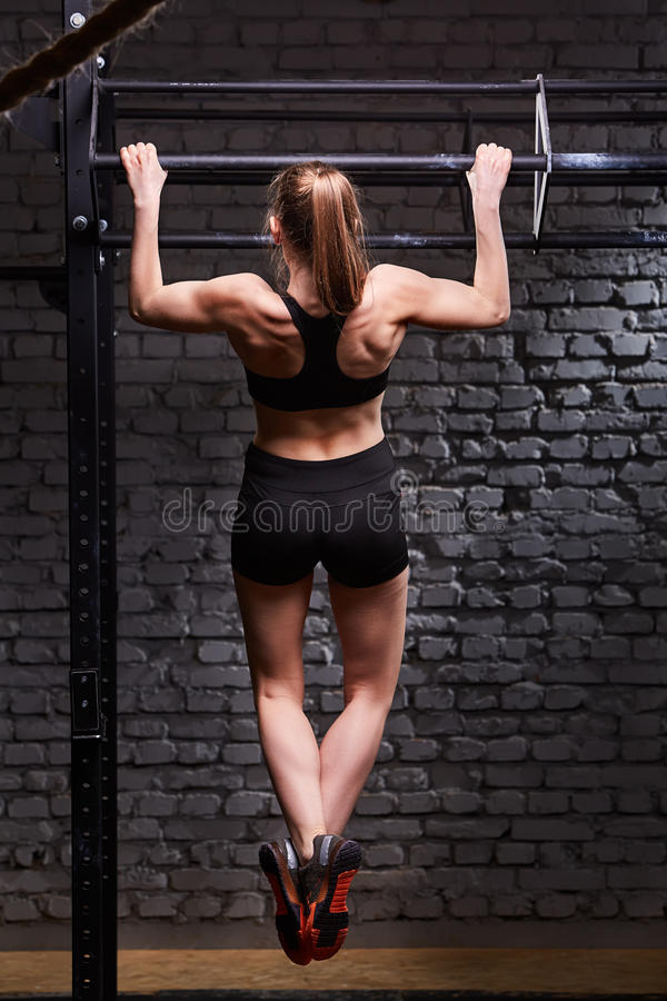 Rear view photo of the young fitness woman pulls up on the horizontal bar against brick wall at the cross fit gym. stock photos