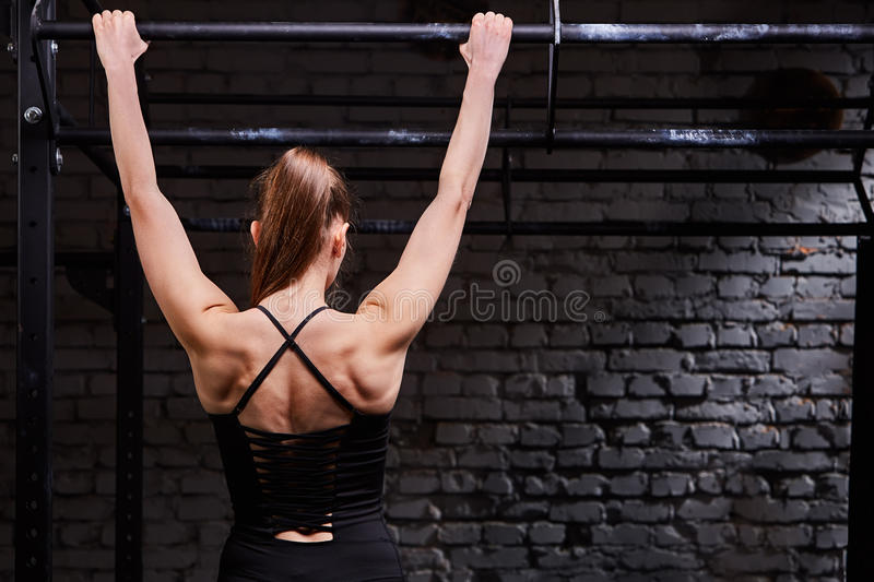 Rear view photo of young muscular woman doing exercises on horizontal bar against brick wall at the cross fit gym. Body and muscle. Power and energy. Healthy royalty free stock image