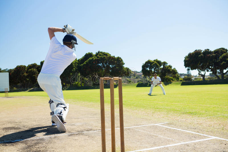 Rear view of player batting while playing cricket on field stock photos