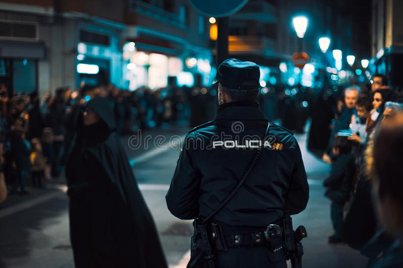 Rear view of Police officer watching during crowded religious event. Holy Week in Zamora, Spain easter week.  royalty free stock photo