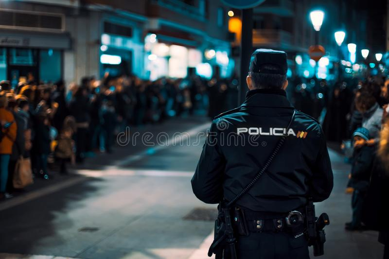 Rear view of Police officer watching during crowded religious event. Holy Week in Zamora, Spain easter week. Rear view of Police officer watching during crowded stock image