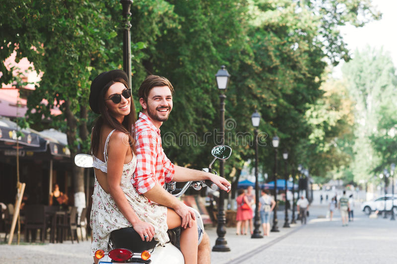 Rear view portrait of happy couple riding a scooter royalty free stock images