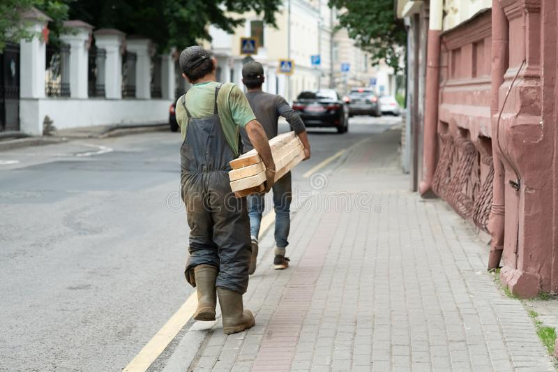 Rear view portrait of mature workman carrying long wooden board moving material in factory workshop royalty free stock photo