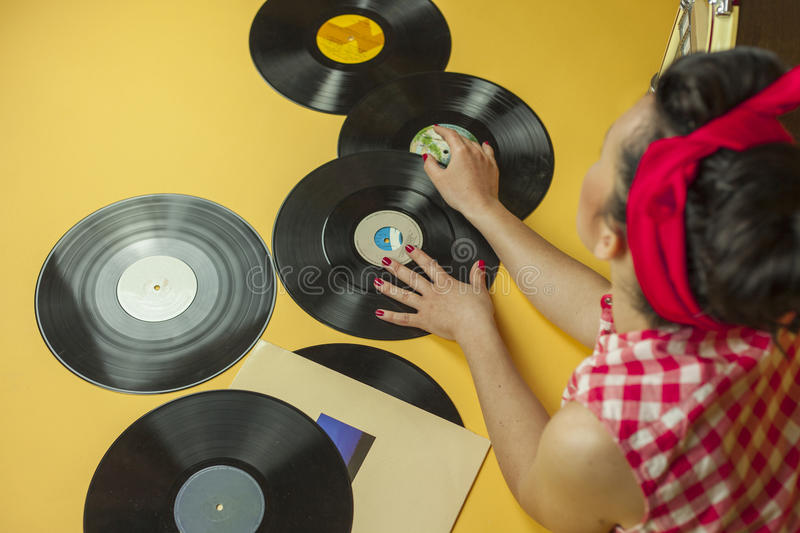 Rear view portrait pin up girl with old vinil records. Selective. Rear view portrait pin up girl with old vinil records, isolated yellow background royalty free stock photography