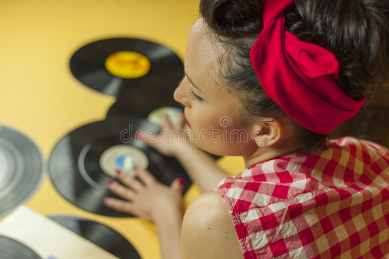 Rear view portrait pin up girl with old vinil records. Selective. Rear view portrait pin up girl with old vinil records, isolated yellow background stock photos