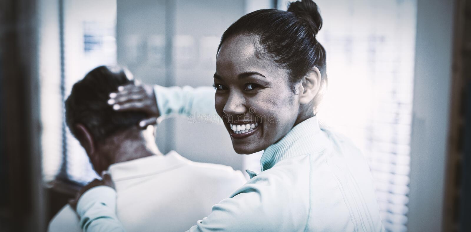Rear view of portrait of smiling female therapist giving neck massaging to senior male patient royalty free stock image