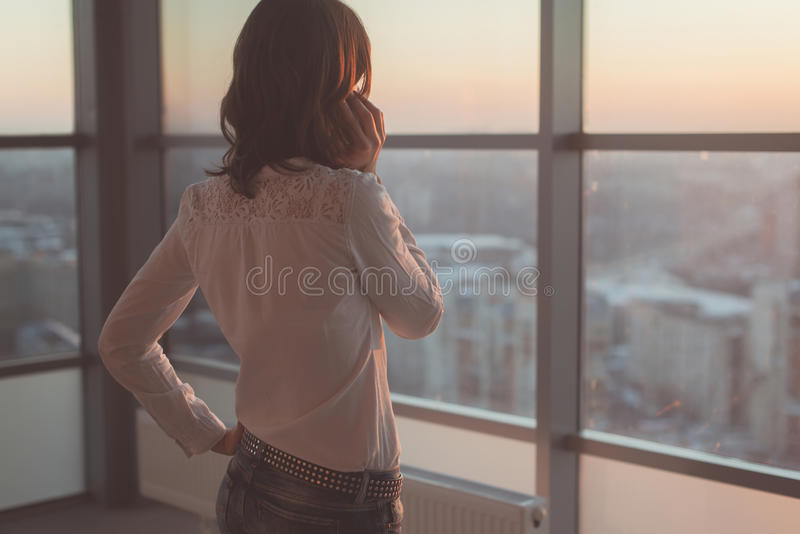 Rear view portrait of young worker speaking using cell phone, looking out the window. Female having business call, busy stock photo