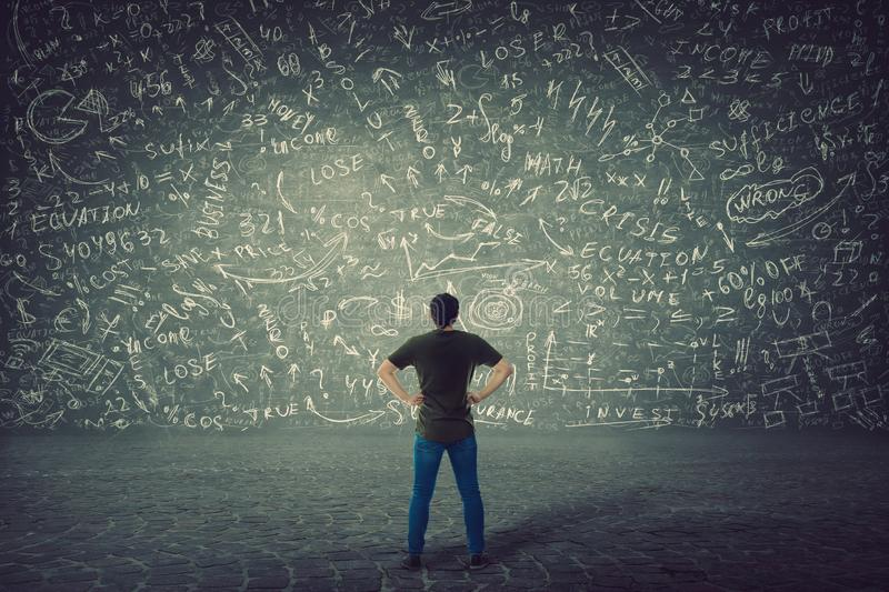 Rear view of puzzled student, hands on hips, stands in front of a huge blackboard try to solve hard mathematics calculation, stock photos