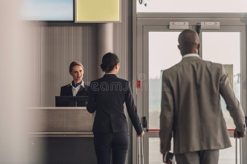 rear view of queue of businesspeople at airport check royalty free stock image