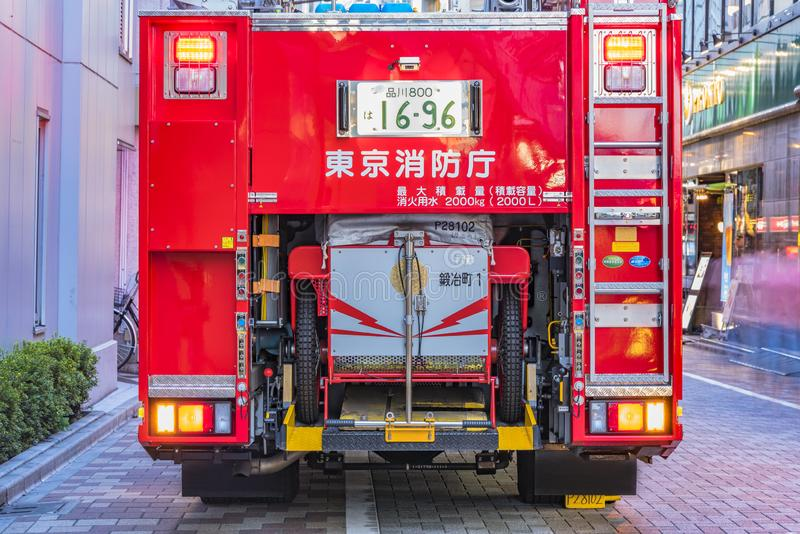 Rear view of a red Japanese fire truck with its lit traffic lights and license plate registered in Shinagawa stock photography