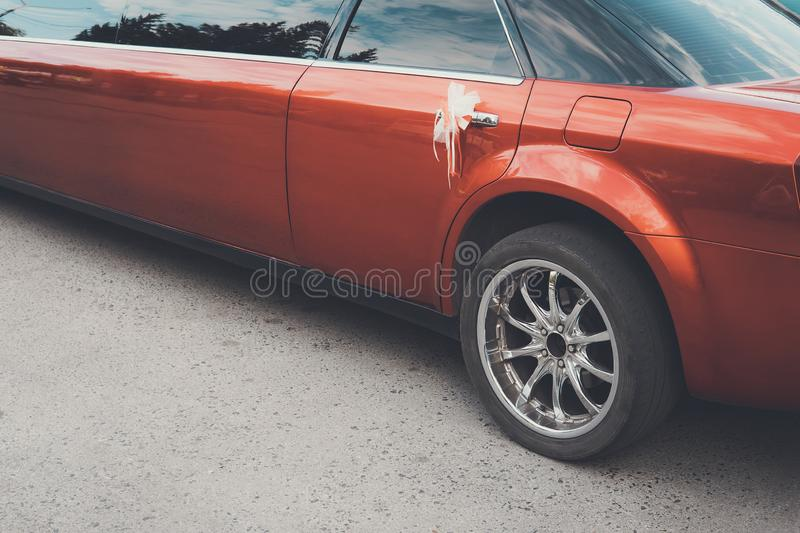 A rear view of a red long limousine with a decoration on the back door handle. The rear part of a festive red limousine royalty free stock images