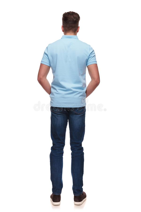 Rear view of relaxed casual man wearing blue polo shirt. While standing on white background, full length picture stock image