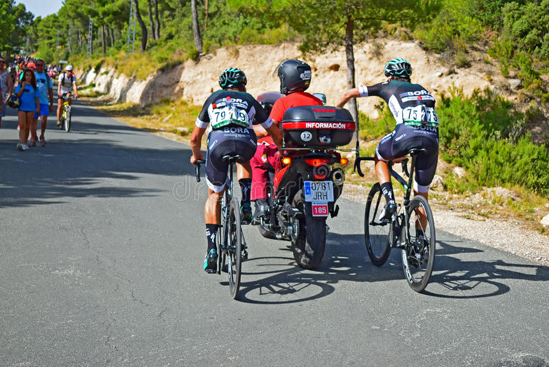 Cycle Racers Holding On To Motorcycle La Vuelta España. A rear view of riders getting a tow up a hill after stage eight Xorret De Cati in the 2017 La Vuelta royalty free stock photo