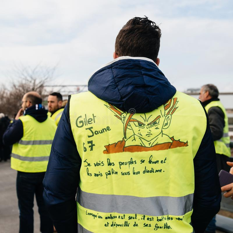 Rear view of riends vearing green yellow vests at protest. STRASBOURG, FRANCE - FEB 02, 2018: Friends demonstrating during protest of Gilets Jaunes Yellow Vest stock photos