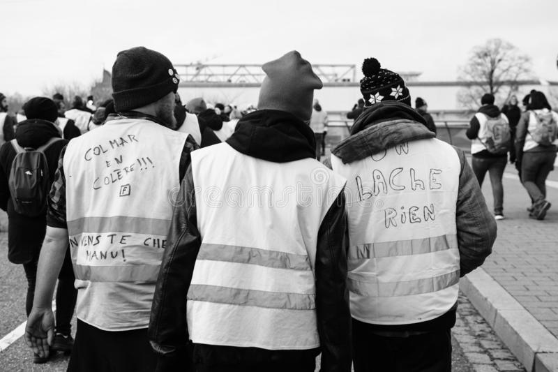 Rear view of riends vearing green yellow vests at protest. STRASBOURG, FRANCE - FEB 02, 2018: Friends demonstrating during protest of Gilets Jaunes Yellow Vest royalty free stock photo