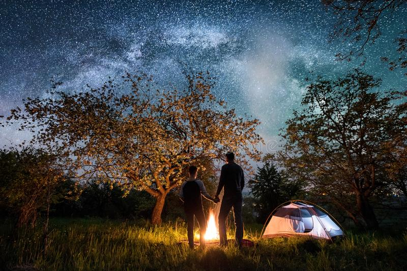 Rear view of couple tourists standing at a campfire, near tent under trees and night sky full of stars and milky way. Rear view of romantic couple tourists royalty free stock photos