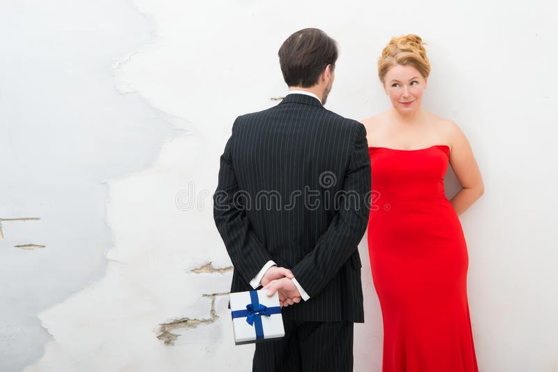 Rear view of romantic man keeping small present for his charming wife stock image
