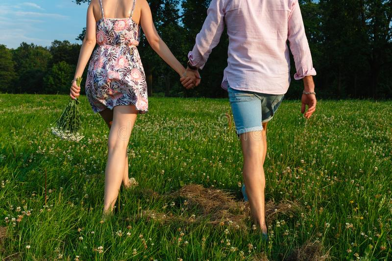 Rear view of a romantic man and woman stand on walk on field grass. Concept of lovely family holding hands. Young couple running t stock photos