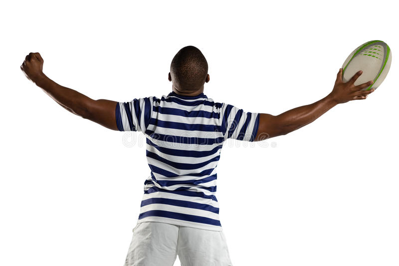Rear view of rugby player with arms outstretched. Standing against white background royalty free stock photography