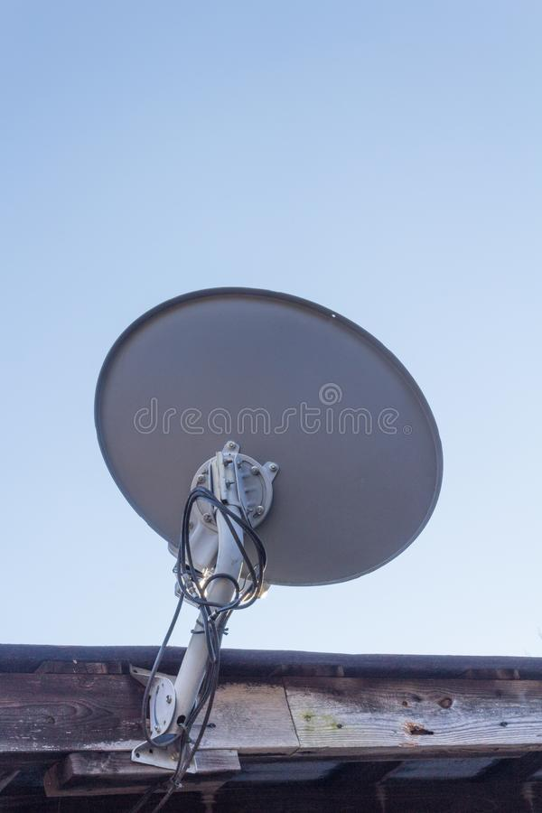 Rear view of a satellite dish mounted to old wood fascia, copy space. Vertical aspect royalty free stock photography