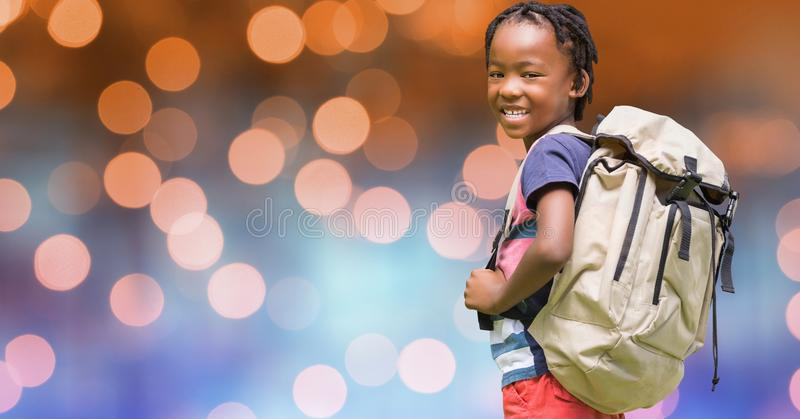 Rear view of school child carrying backpack over bokeh royalty free stock photography