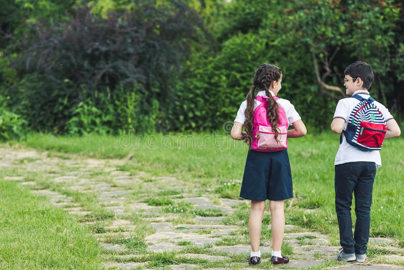 Rear view of schoolchildren walking by pathway. In park together stock images