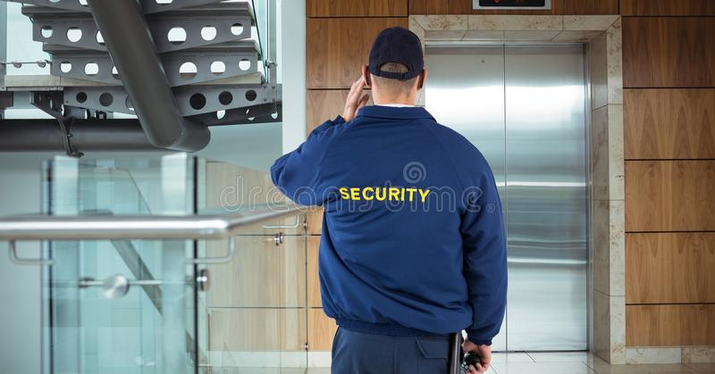 Rear view of security guard waiting for lift while standing in office building stock images
