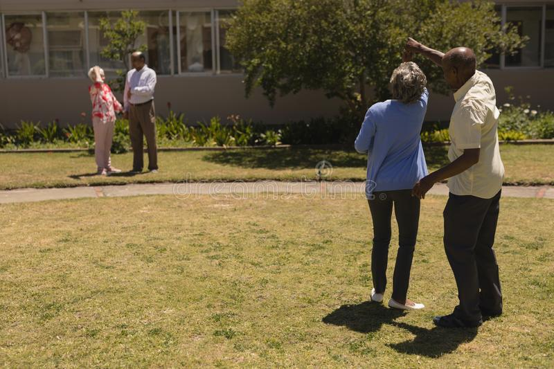 Rear view of senior couple dancing together in garden royalty free stock image