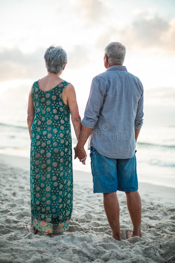 Rear view of a senior couple holding hands royalty free stock photography
