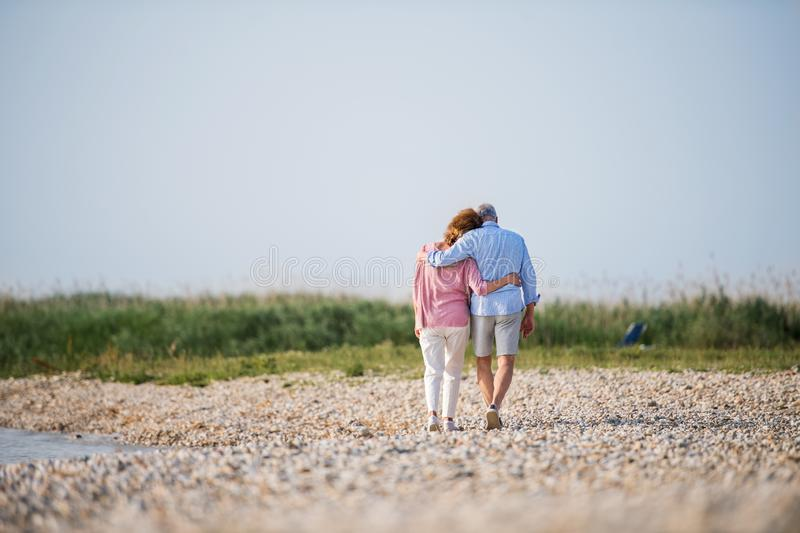 Rear view of senior couple on a holiday on a walk by the lake, walking. Rear view of senior couple on a holiday on a walk by the lake, walking arm in arm royalty free stock photo