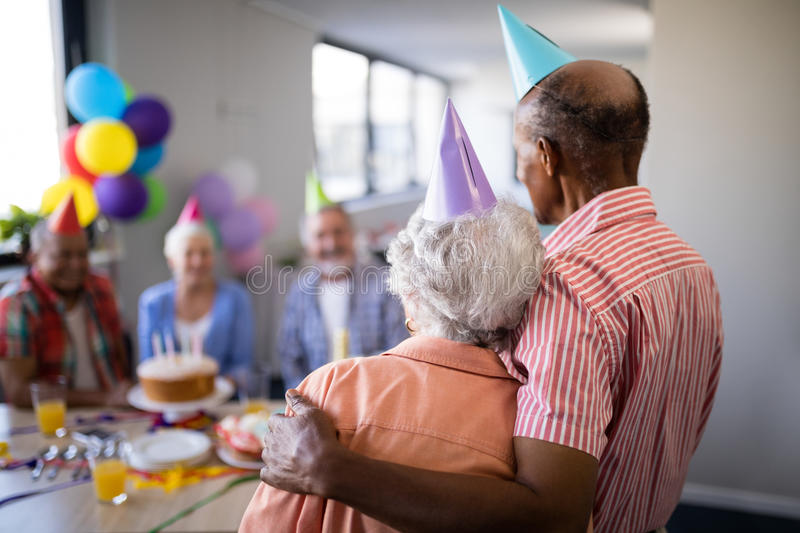 Rear view of senior couple looking at friends during party. Rear view of senior couple looking at friends sitting by table during birthday celebration royalty free stock photo