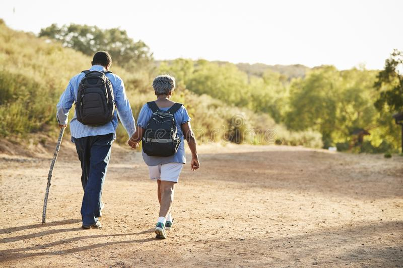 Rear View Of Senior Couple Wearing Backpacks Hiking In Countryside Together royalty free stock photo